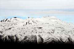 Mauna Kea summit showing observatories.  Shot from south side of mountain. Road to summit visible.